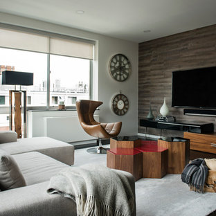 Trendy dark wood floor living room photo in New York with gray walls and a wall-mounted tv