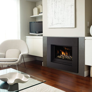 Design ideas for a small contemporary living room in Vancouver with grey walls, a ribbon fireplace, a metal fireplace surround, medium hardwood floors and a corner tv.
