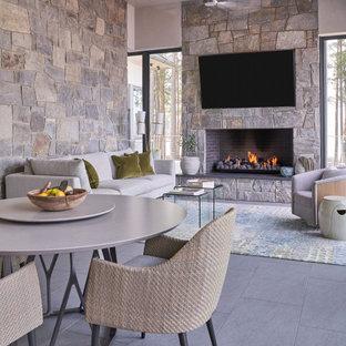 ヒューストンのコンテンポラリースタイルのおしゃれなLDK (グレーの壁、標準型暖炉、石材の暖炉まわり、壁掛け型テレビ、グレーの床、塗装板張りの天井) の写真