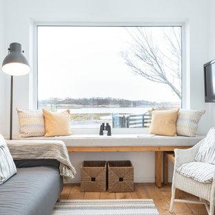 Ejemplo de biblioteca en casa abierta, contemporánea, pequeña, con paredes blancas, suelo de madera en tonos medios, estufa de leña, marco de chimenea de piedra, televisor colgado en la pared y suelo marrón