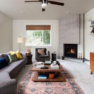 Immagine di un soggiorno minimal di medie dimensioni e aperto con pareti bianche, moquette, camino ad angolo, cornice del camino piastrellata, TV a parete e pavimento grigio