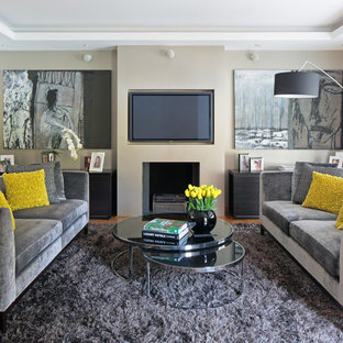 Contemporary living room in London with beige walls and a wall mounted tv.