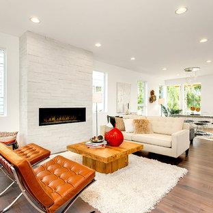Modelo de salón para visitas abierto, actual, de tamaño medio, sin televisor, con paredes blancas, suelo de madera clara, chimenea lineal y marco de chimenea de ladrillo