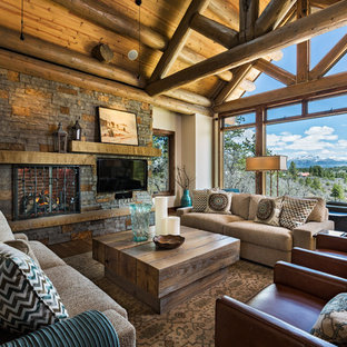 Example of a large mountain style open concept medium tone wood floor living room design in Albuquerque with beige walls, a wood stove, a stone fireplace and a media wall