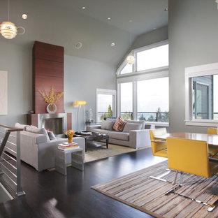 Idee per un soggiorno minimal con pareti grigie, camino classico e pavimento marrone