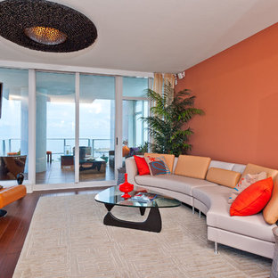 Example of a trendy living room design in Tampa with orange walls and a wall-mounted tv