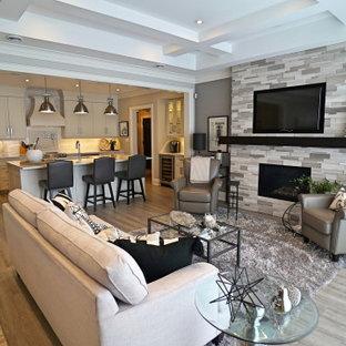 Mittelgroßes, Offenes Modernes Wohnzimmer mit grauer Wandfarbe, Vinylboden, Kamin, Kaminumrandung aus gestapelten Steinen, Wand-TV und grauem Boden in Toronto