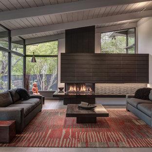 Inspiration för stora retro allrum med öppen planlösning, med ett finrum, grå väggar, ljust trägolv, en öppen hörnspis, en spiselkrans i sten och grått golv