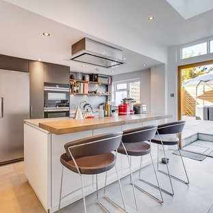 This is an example of a contemporary kitchen in London with flat-panel cabinets, grey cabinets, grey splashback, an island and grey floors.