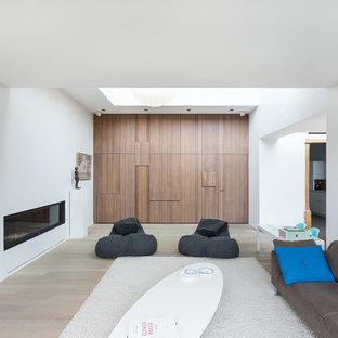 Inspiration för minimalistiska separata vardagsrum, med ett finrum, vita väggar, ljust trägolv och en bred öppen spis
