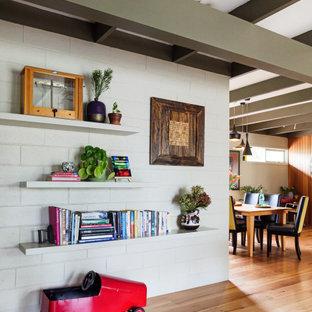 Aménagement d'un grand salon contemporain ouvert avec un sol en bois brun, un poêle à bois, un manteau de cheminée en brique, un téléviseur fixé au mur, un plafond en poutres apparentes et un mur en parement de brique.