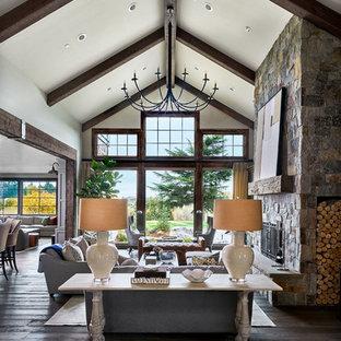Réalisation d'un grand salon champêtre ouvert avec un mur blanc, un sol en bois brun, une cheminée standard et un manteau de cheminée en pierre.