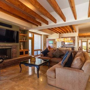 フェニックスの大きいサンタフェスタイルのおしゃれなLDK (マルチカラーの壁、ライムストーンの床、標準型暖炉、石材の暖炉まわり、壁掛け型テレビ、ベージュの床) の写真