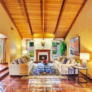 Foto di un soggiorno stile americano di medie dimensioni con sala formale, pareti gialle, pavimento in terracotta, camino classico, cornice del camino in intonaco e pavimento multicolore