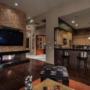 Ispirazione per un grande soggiorno design aperto con pareti multicolore, parquet scuro, camino bifacciale, cornice del camino piastrellata e TV a parete