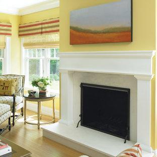 ボストンのヴィクトリアン調のおしゃれなリビング (黄色い壁、淡色無垢フローリング、標準型暖炉) の写真