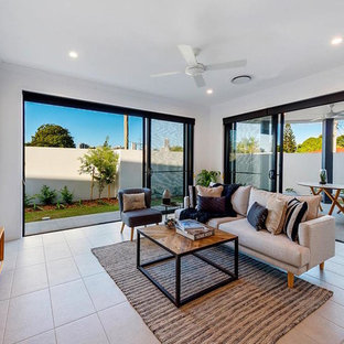 This is an example of a mid-sized contemporary formal open concept living room in Gold Coast - Tweed with white walls, ceramic floors, a freestanding tv and beige floor.