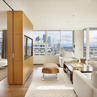 Ejemplo de salón para visitas abierto, moderno, de tamaño medio, con paredes blancas, suelo de madera en tonos medios y pared multimedia
