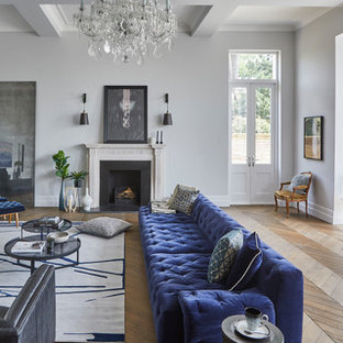 Large classic open plan living room in Hertfordshire with grey walls, a standard fireplace, a plastered fireplace surround, a wall mounted tv and medium hardwood flooring.