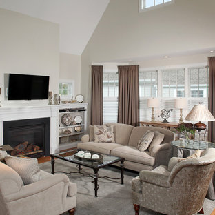 Inspiration for a mid-sized timeless open concept medium tone wood floor living room remodel in Boston with gray walls, a standard fireplace and a wall-mounted tv