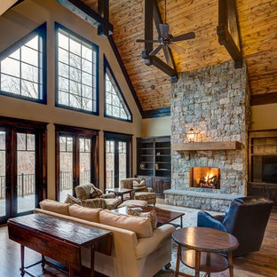 This is an example of a large arts and crafts formal open concept living room in Atlanta with beige walls, dark hardwood floors, a standard fireplace, a stone fireplace surround and a built-in media wall.
