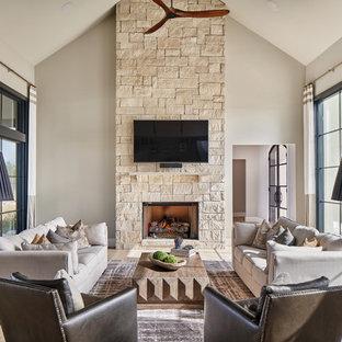 Foto di un soggiorno classico aperto con pareti bianche, parquet chiaro, camino classico, cornice del camino in pietra, TV a parete e pavimento marrone