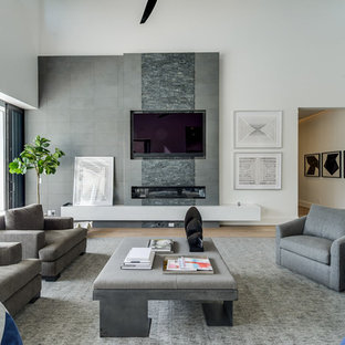 Photo of a contemporary open plan living room in Miami with white walls, medium hardwood flooring, a ribbon fireplace, a tiled fireplace surround, a wall mounted tv and brown floors.
