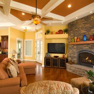ワシントンD.C.のトラディショナルスタイルのおしゃれなリビング (黄色い壁、コーナー設置型暖炉、石材の暖炉まわり、壁掛け型テレビ) の写真