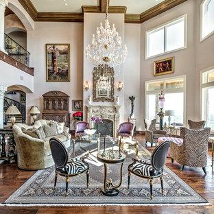 Idee per un ampio soggiorno mediterraneo aperto con pareti viola, parquet scuro, sala formale, camino classico, cornice del camino in pietra, nessuna TV e pavimento marrone