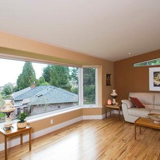 Modelo de salón para visitas abierto, contemporáneo, grande, sin televisor, con paredes amarillas, suelo de madera clara, estufa de leña y marco de chimenea de piedra
