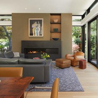 Modelo de salón abierto, actual, grande, sin televisor, con paredes blancas, suelo de madera en tonos medios, chimenea lineal, marco de chimenea de hormigón y suelo marrón