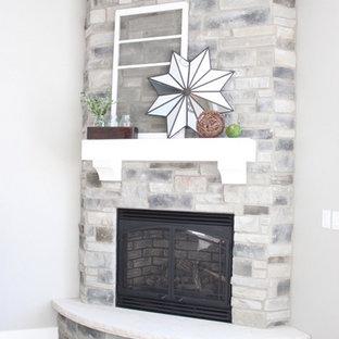 他の地域の中くらいのトラディショナルスタイルのおしゃれなリビング (グレーの壁、コーナー設置型暖炉、石材の暖炉まわり、テレビなし) の写真