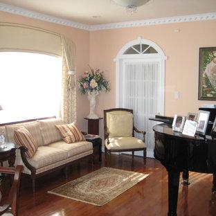 Inredning av ett klassiskt litet allrum med öppen planlösning, med ett musikrum, rosa väggar, mellanmörkt trägolv och brunt golv