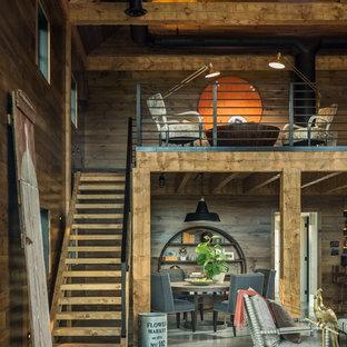 Ispirazione per un soggiorno country stile loft con pavimento in cemento e camino bifacciale