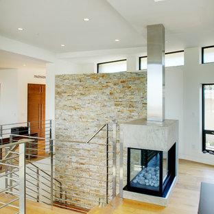 オレンジカウンティの中サイズのコンテンポラリースタイルのおしゃれなリビングロフト (白い壁、淡色無垢フローリング、両方向型暖炉、コンクリートの暖炉まわり、埋込式メディアウォール) の写真