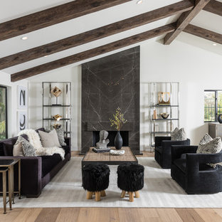Example of a transitional open concept medium tone wood floor and brown floor living room design in Los Angeles with white walls and a standard fireplace