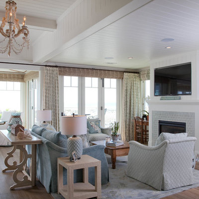 Living room - huge coastal open concept medium tone wood floor living room idea in San Diego with white walls, a standard fireplace, a wall-mounted tv and a brick fireplace
