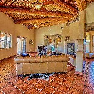 Esempio di un ampio soggiorno stile americano aperto con pareti beige, pavimento con piastrelle in ceramica, camino classico e cornice del camino in intonaco