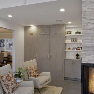 Foto di un piccolo soggiorno moderno con pavimento in pietra calcarea, pareti bianche, camino sospeso e cornice del camino in pietra