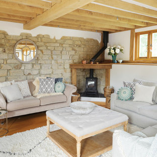 Design ideas for a rural living room in Kent with white walls, medium hardwood flooring and a wood burning stove.