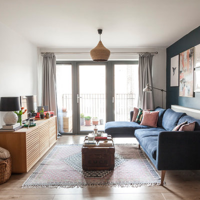 Inspiration for an eclectic brown floor living room remodel in London with blue walls and a tv stand