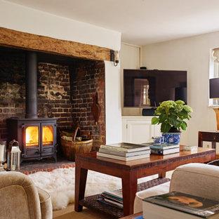 Immagine di un soggiorno country con pareti bianche, stufa a legna, cornice del camino in mattoni e porta TV ad angolo