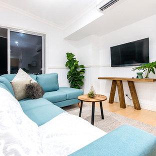 Réalisation d'un salon tradition de taille moyenne et ouvert avec un mur blanc, un sol en bois clair, un téléviseur fixé au mur, un plafond voûté et du lambris de bois.