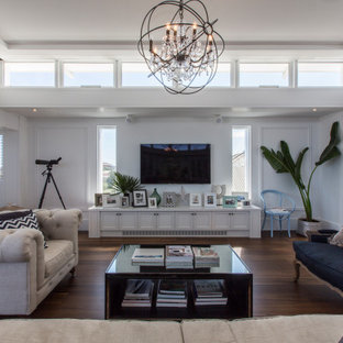Photo of a large beach style open concept living room in Perth with white walls, medium hardwood floors, a wall-mounted tv, brown floor and decorative wall panelling.