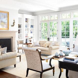 ソルトレイクシティの広いトラディショナルスタイルのおしゃれなLDK (白い壁、濃色無垢フローリング、標準型暖炉、コンクリートの暖炉まわり、テレビなし、茶色い床、フォーマル) の写真