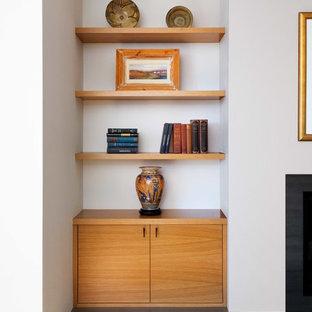 Exempel på ett mellanstort modernt loftrum, med ett finrum, vita väggar, mellanmörkt trägolv, en standard öppen spis och en spiselkrans i metall