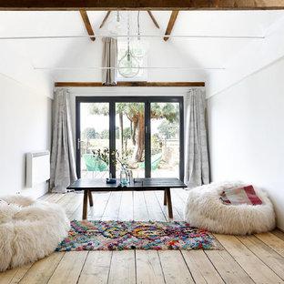 Foto på ett litet rustikt allrum med öppen planlösning, med ett finrum, vita väggar och mellanmörkt trägolv