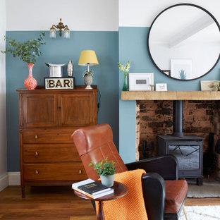 他の地域の中くらいのエクレクティックスタイルのおしゃれなリビングのホームバー (青い壁、無垢フローリング、薪ストーブ、茶色い床) の写真