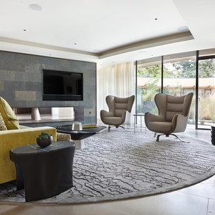 Esempio di un grande soggiorno contemporaneo aperto con pareti multicolore, pavimento in pietra calcarea, camino bifacciale, cornice del camino in pietra, TV a parete e pavimento beige