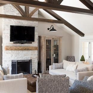 Inredning av ett klassiskt stort allrum med öppen planlösning, med vita väggar, mörkt trägolv, en standard öppen spis, en väggmonterad TV, en spiselkrans i sten och brunt golv